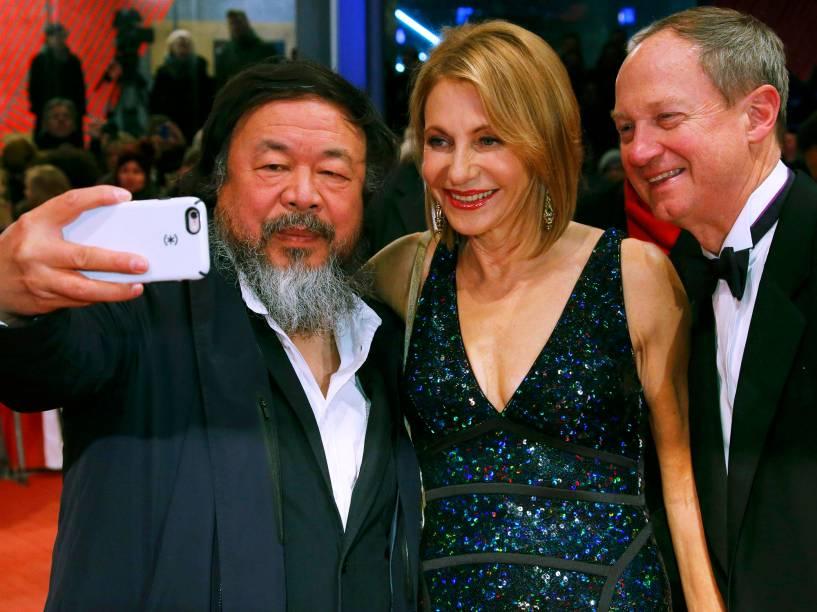 Artista chinês Ai Weiwei, posa para selfie com o embaixador americano na Alemanha, John Emerson, e sua esposa Kimberly, ao chegar no tapete vermelho, para a exibição do filme Ave, César, durante a abertura de gala do Festival de cinema de Berlim, nesta quinta (11)