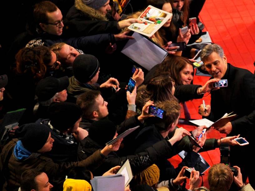 Ator americano George Clooney, posa para foto com uma fã, na chegada ao tapete vermelho. O filme Ave, César, protagonizado por ele, será exibido na abertura do Festival de cinema de Berlim, na Alemanha, nesta quinta (11)