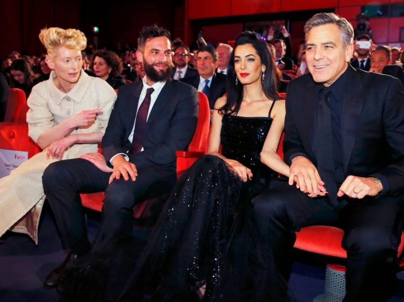 Ator americano George Clooney, e sua esposa Amal Alamuddin, ao lado dos atores Tilda Swinton e Sandro Kopp, tomam os seus lugares na abertura de gala do Festival Internacional de cinema de Berlim, na Alemanha, na noite desta quinta-feira (11)