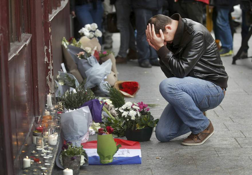 Homem chora em frente ao restaurante Le Carillon, em Paris