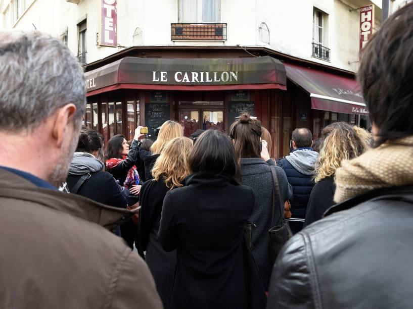 Pessoas fazem minuto de silêncio em frente ao restaurante Carillon, local de um dos ataques terroristas simultâneos em Paris
