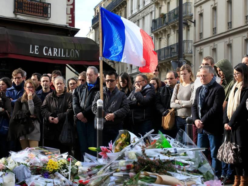 Pessoas fazem minuto de silêncio em homenagens às vítimas em frente ao restaurante Le Carillon, em Paris (França), nesta segunda-feira