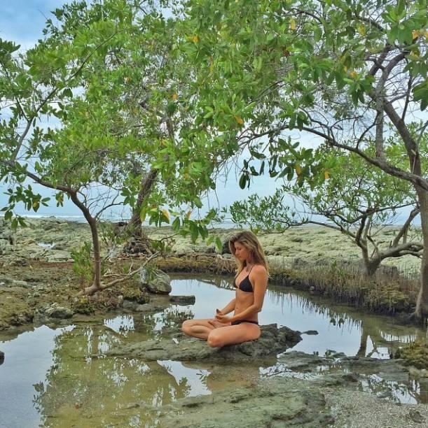 Gisele Bündchen medita, sentada, de biquíni preto sobre a lama, em uma praia não identificada