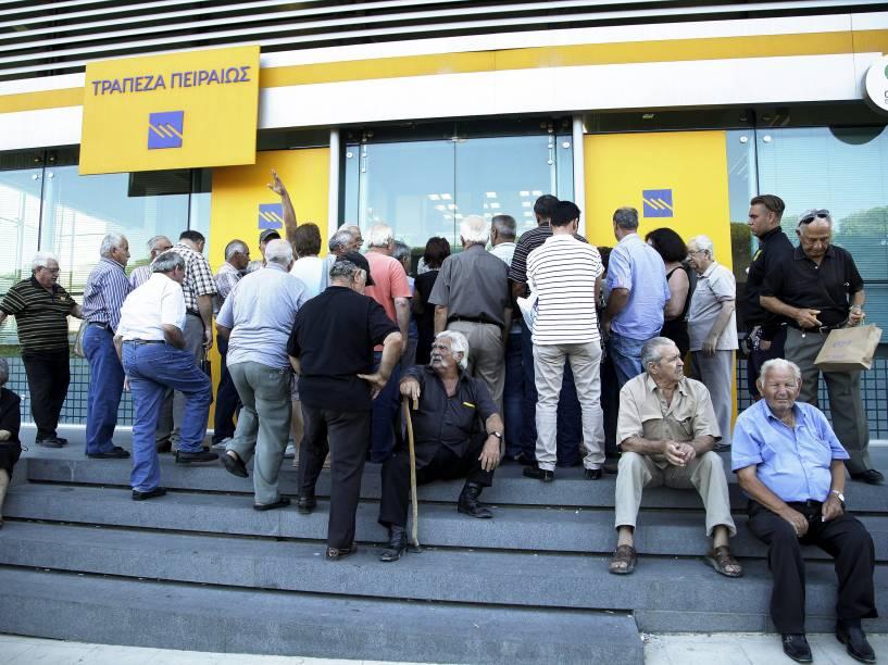 Em Heraklion, na ilha grega de Creta, pensionistas aguardam a abertura de uma agência bancária. Após três semanas os bancos reabrem na Grécia; porém, o controle de capital ainda é mantido - 20/07/2015