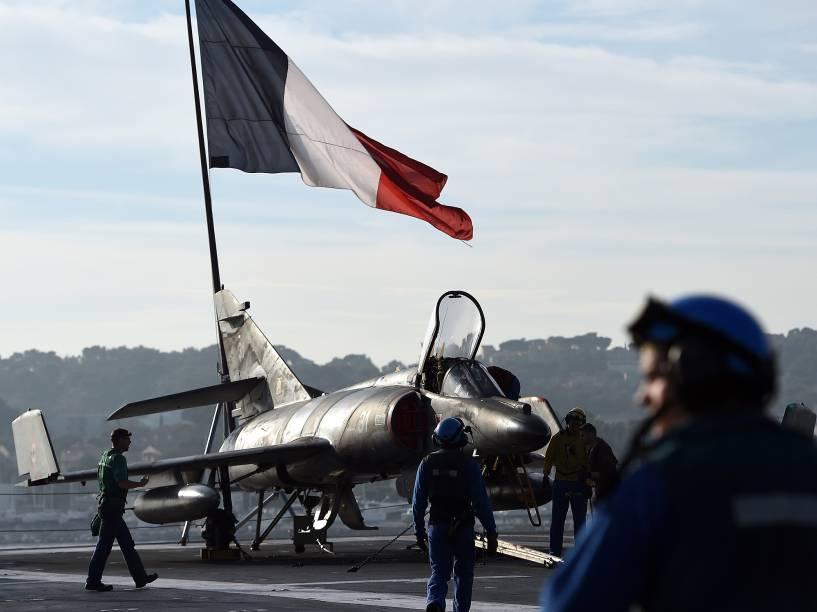 Soldados preparam um avião-caça Rafale no porta-aviões Charles de Gaulle, em Toulon, sul da França