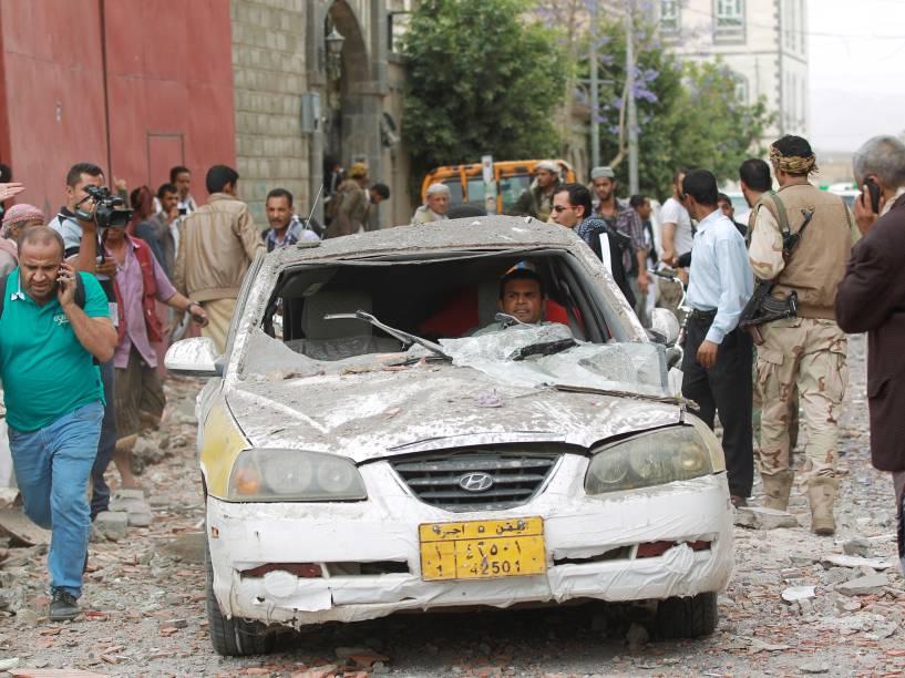 Homem senta em seu carro danificado por ataques aéreos realizados pela coalizão árabe contra os rebeldes houthis xiitas e seus aliados, na capital Sana