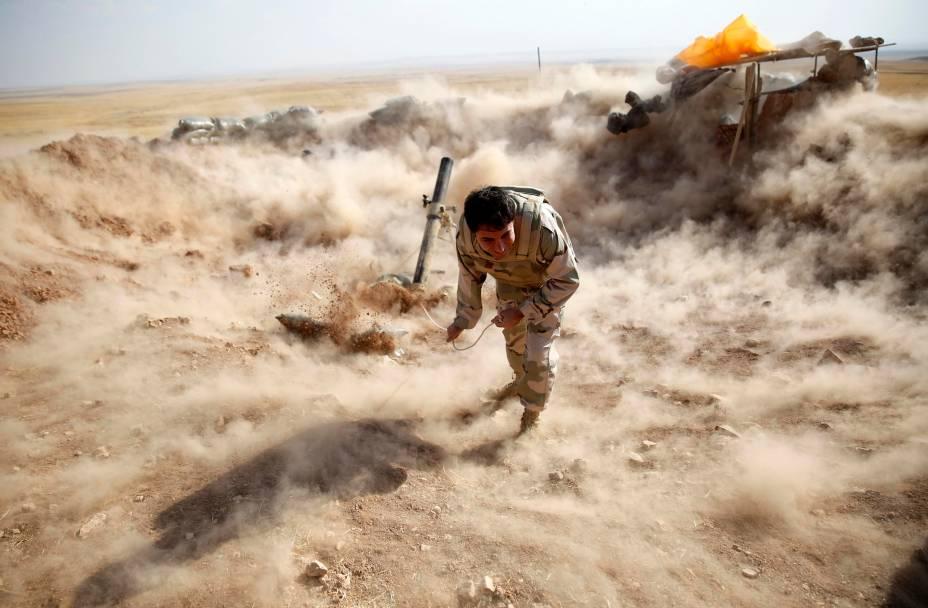 Combatente curdo Peshmerga lança morteiro em direção a cidade de Zummar, controlada pelo Estado Islâmico, no Iraque