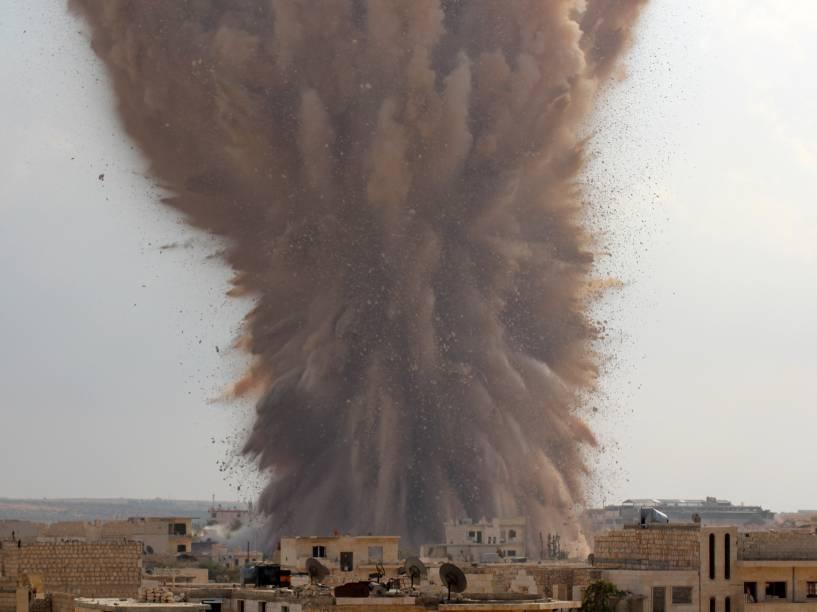 Na imagem, um posto militar do exército sírio localizado na cidade de Maarat al-Numan é atingido por combatentes rebeldes do Estado Islâmico (EI), nesta terça-feira (14)