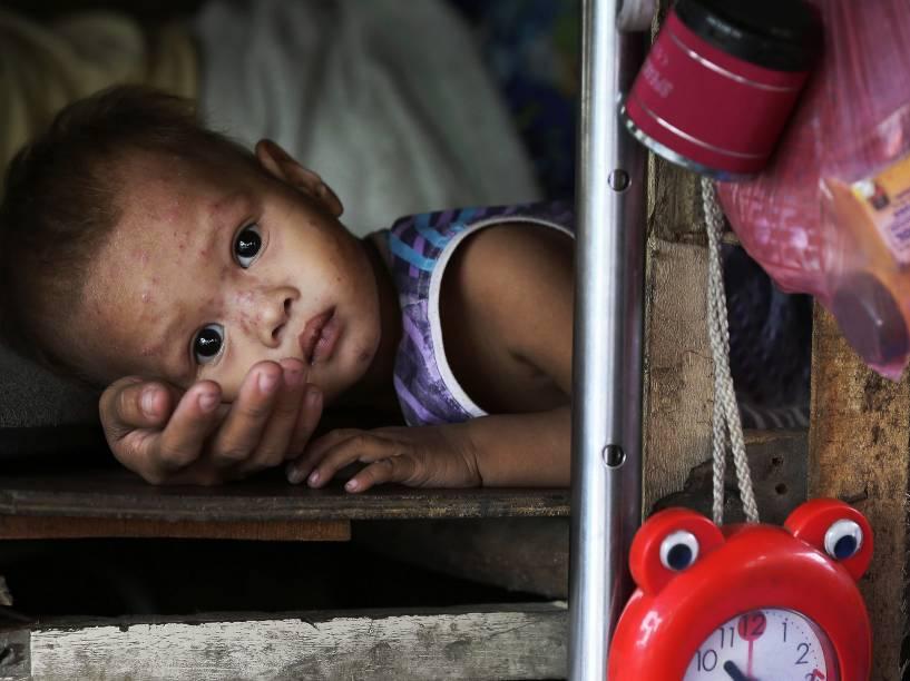 Criança descansa no colo da mãe em sua cabana enquanto espera para serem evacuados de uma favela de Baseco, em Manila, nas Filipinas em decorrência da chegada do super tufão Hagupit - 05/12/2014