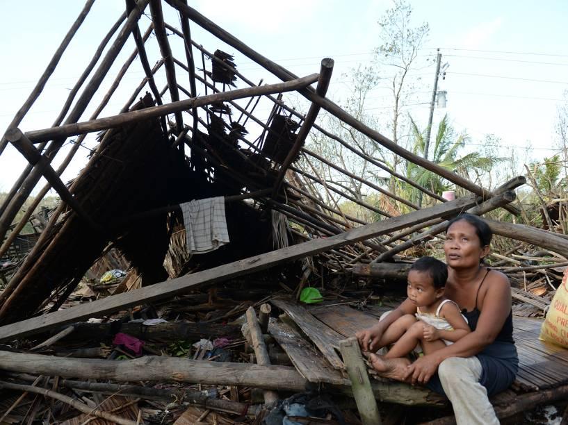 Nas Filipinas, sobreviventes ao lado de sua casa destruída pelo tufão Hagupit. Pelo menos 21 pessoas morreram e mais de um milhão foram para abrigos para se proteger da tempestade