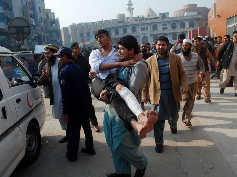 Homem carrega estudante ferido após ataque no Paquistão