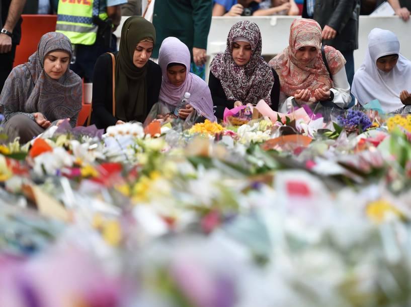 Jovens depositam flores em memorial em frente ao local onde um homem armado fez reféns e deixou mortos na véspera no centro do distrito financeiro de Sydney, na Austrália