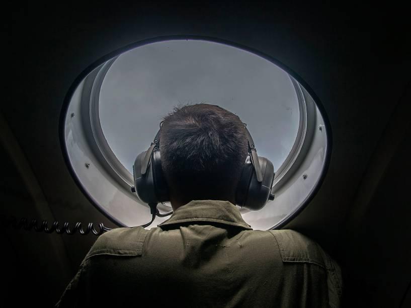 Membro das forças armadas da Indonésia olha da janela de uma aeronave durante operação de busca e salvamento do voo QZ8501 da AirAsia, sobre as águas do mar de Java - 29/12/2014