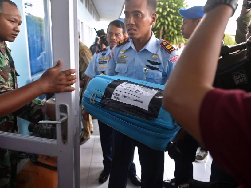 Membro da força aérea indonésia carrega um item recuperado do mar de Java durante as operações de busca e salvamento da aeronave da AirAsia, em Pangkalan Bun, na Indonésia - 30/12/2014
