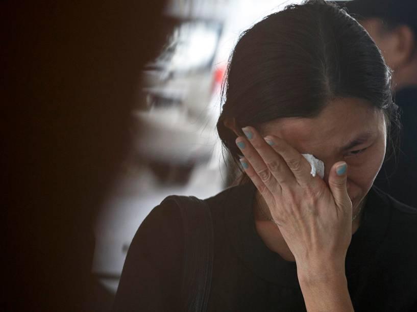 Familiar de um passageiro do voo AirAsia QZ8501 chora em um crematório de Surabaya, na Indonésia. Os corpos das 162 vítimas da tragédia estão sendo resgatados no mar de Java em uma ação das Forças Nacionais