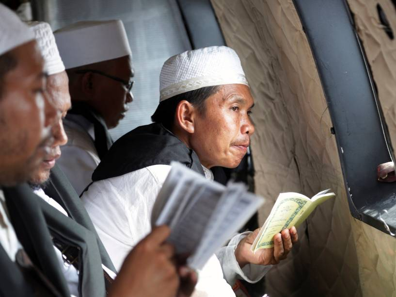 Clérigo muçulmano faz uma pausa enquanto ele lê versos do Alcorão durante uma oração para as vítimas do voo AirAsia QZ8501, dentro de um helicóptero da Força Aérea da Indonésia que sobrevoa o mar de Java em busca de vítimas e partes da aeronave - 06/01/2015