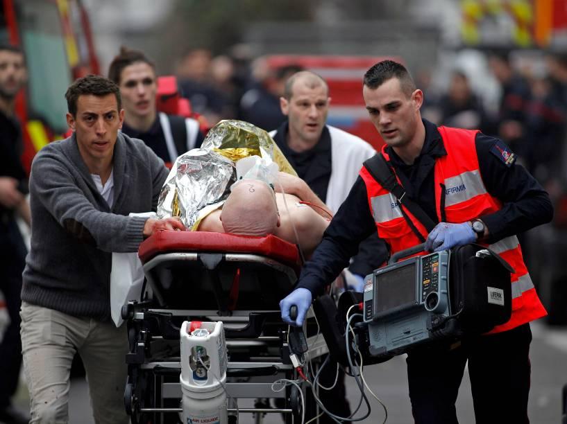 Bombeiros resgatam um ferido depois que homens armados invadiram o escritório do jornal satírico Charlie Hebdo, em Paris, na França. Ao menos 12 pessoas morreram durante o ataque