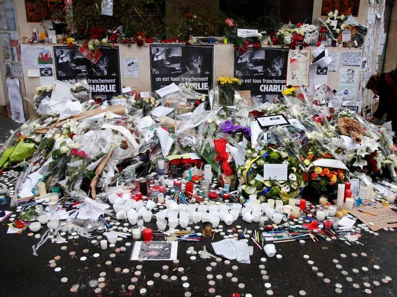 Velas, canetas, cadernos, lápis e flores são postos em frente à sede do jornal francês satírico Charlie Hebdo, em homenagem às vítimas dos ataques ao local