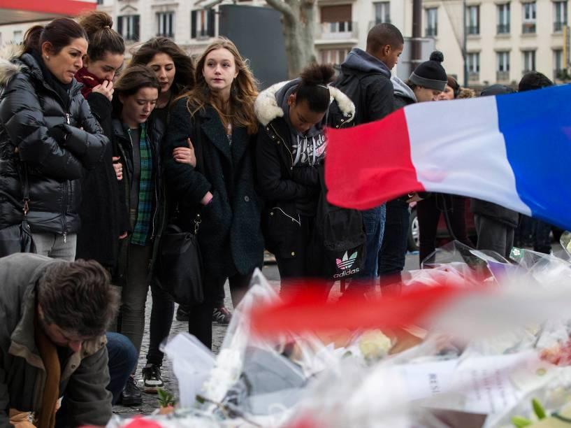 Pessoas deixam flores, velas e mensagens em frente ao mercado kosher onde quatro reféns foram mortos, em Paris , na França