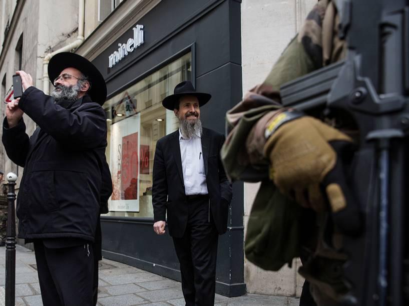 Judeus observam a circulação de policiais frances que reforçam a segurança no bairro de Marais, em Paris