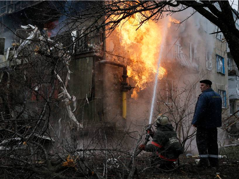 Bombeiro tenta combater incêndio em uma casa que foi bombardeada em Donetsk, leste da Ucrânia