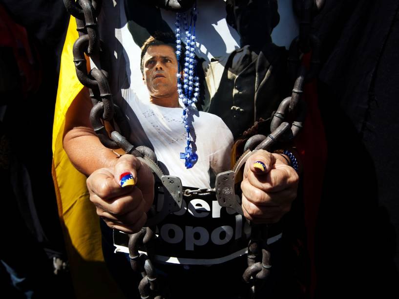 Mulher usa algemas, correntes e um rosário sobre um cartaz do líder da oposição Leopoldo Lopez durante uma manifestação marcando o aniversário de um ano de sua detenção e prisão, em Caracas, na Venezuela - 18/02/2015