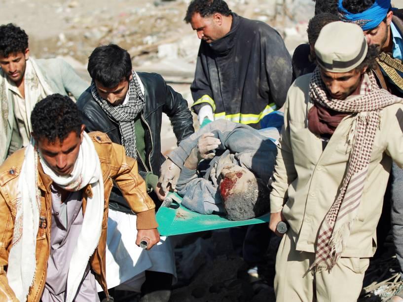Homens carregam um ferido após retirá-lo dos escombros de uma casa destruída por bombardeio perto do aeroporto de Sana, no Iêmen - 26/03/2015