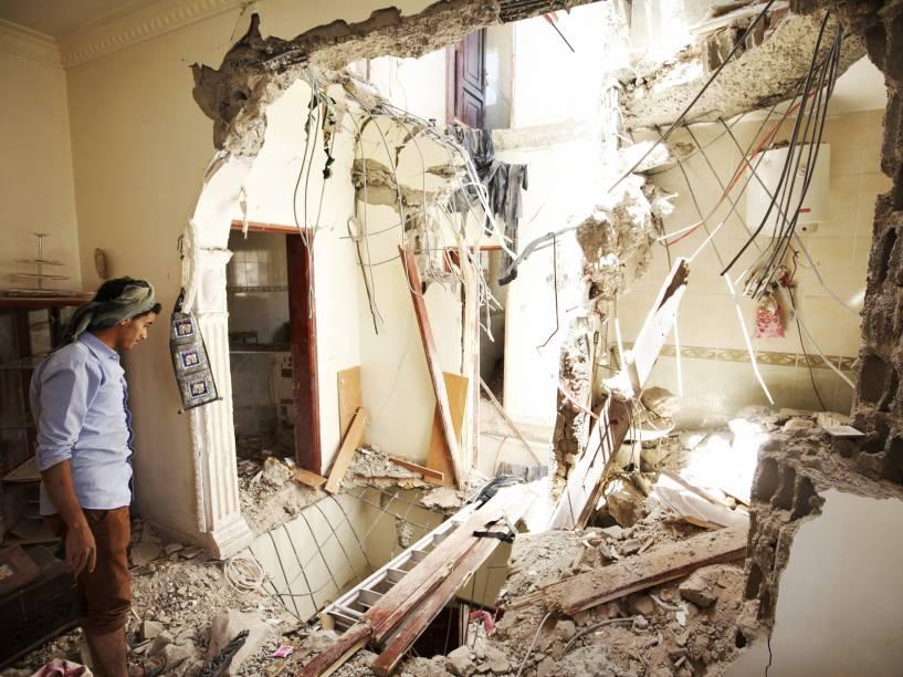 Homem observa os danos causados em sua casa após ataque aéreo em Sanaa, no Iêmen - 20/04/2015