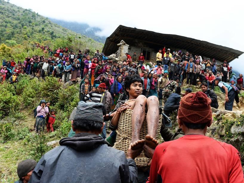 Homem ferido no terremoto do último sábado, é carregado por nepaleses até um helicóptero na vila de Uiya, no Nepal