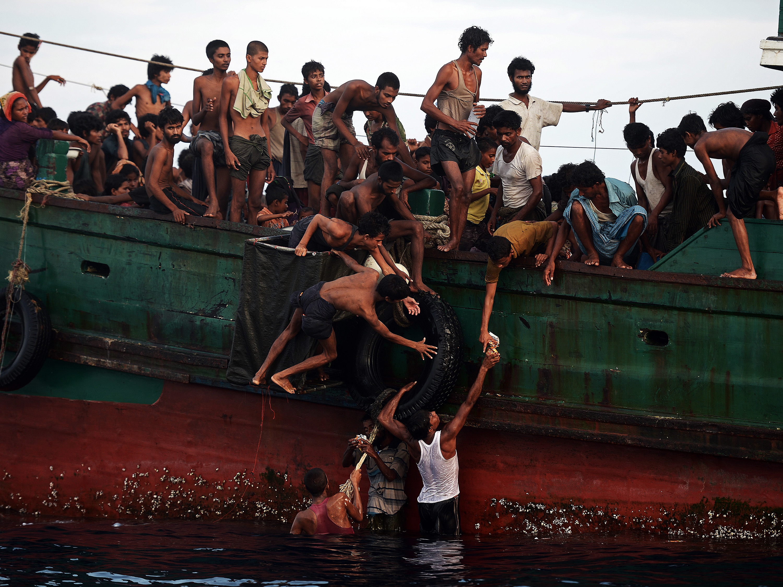 Migrantes da etnia muçulmana Rohingya presos em um barco à deriva tentam recolher os alimentos lançados por um helicóptero do exército tailandês ao largo da ilha do sul de Koh Lipe no mar de Andaman, na Tailândia - 14/05/2015