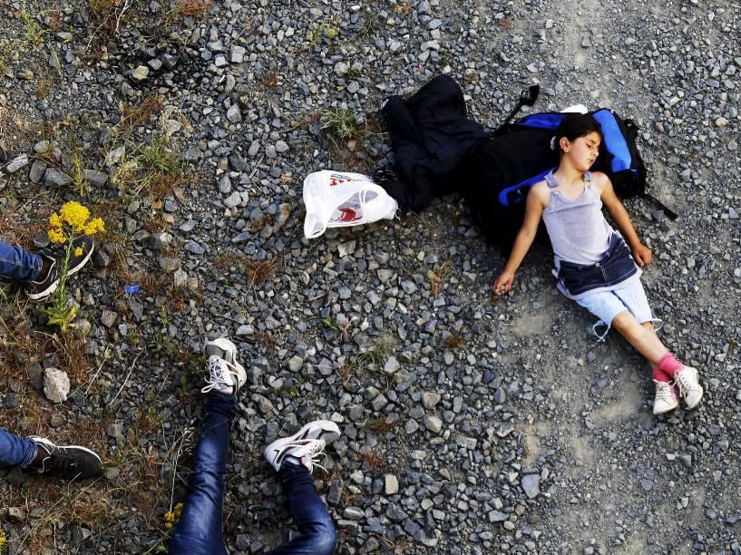 Menina descansa antes de cruzar a Macedônia juntamente com outros 45 imigrantes sírios - 15/05/2015