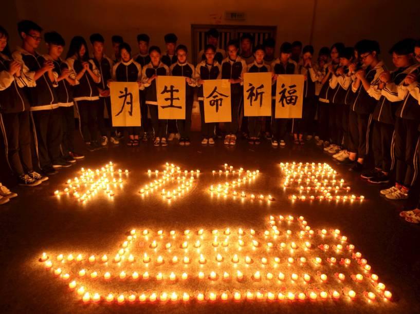 """Estudantes fazem orações por passageiros de cruzeiro. Equipes de mergulhadores procuram cerca de 400 pessoas desaparecidas no naufrágio no rio Yang Tsé, na China. Em chinês, lê-se """"Reze pela vida"""" - 03/06/2015"""