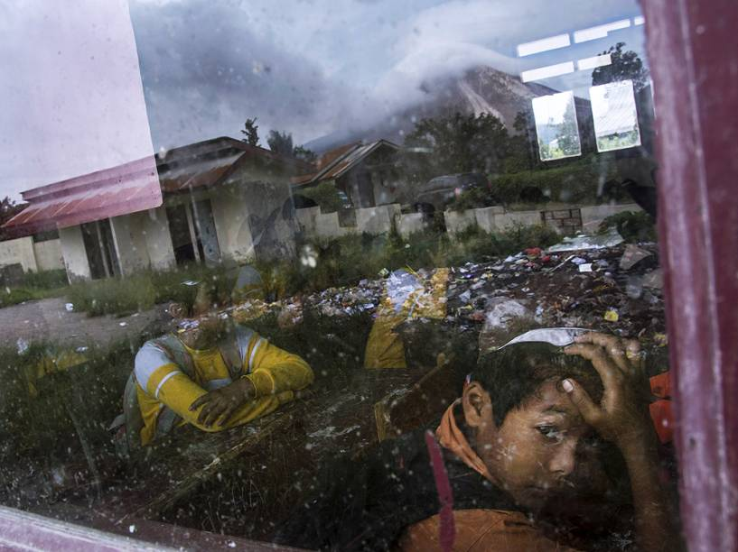 <p>Estudante indonésio é fotografado, com o reflexo do vulcão Sinabung expelindo fumaça visto no vidro, em Karo, na ilha de Sumatra, nesta sexta-feira (12)</p>