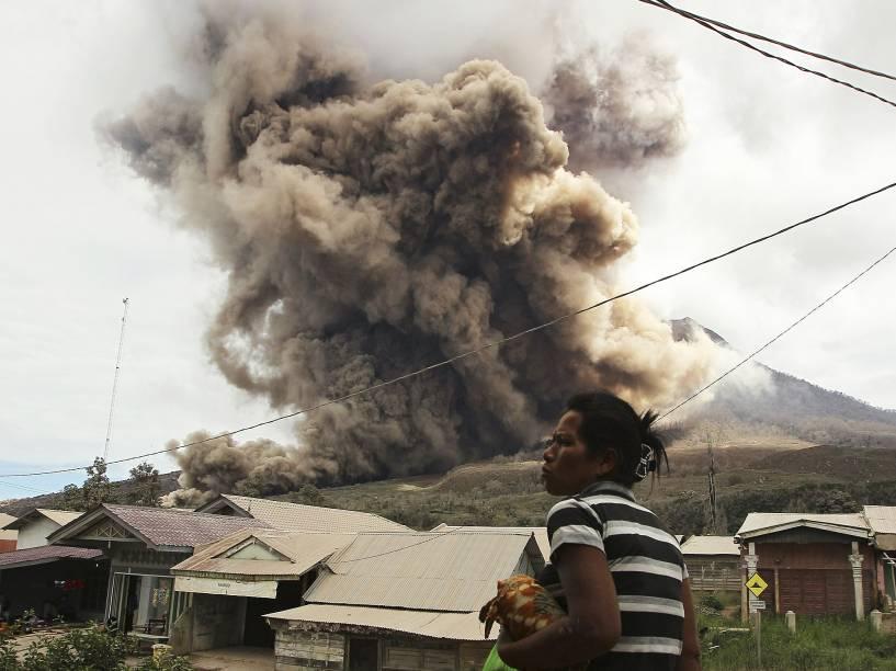 <p>Mulher observa erupção do vulcão do Monte Sinabung, em Tiga Kicat, região norte da Indonésia. Sinabung está entre os 130 vulcões ativos no país e está em atividade desde de 2010, depois de permanecer adormecido por 400 anos</p>
