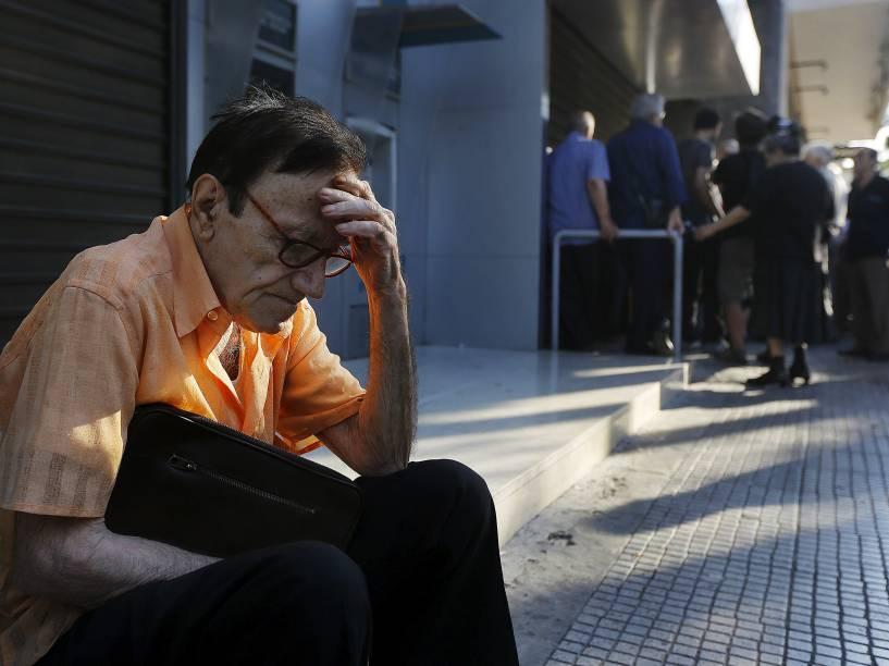 Giorgos, um aposentado de 77 anos, fica fora de uma sucursal do Banco Nacional da Grécia em Atenas, enquanto espera, juntamente com dezenas de outros pensionistas, na esperança de obter seus benefícios - 29/06/2015