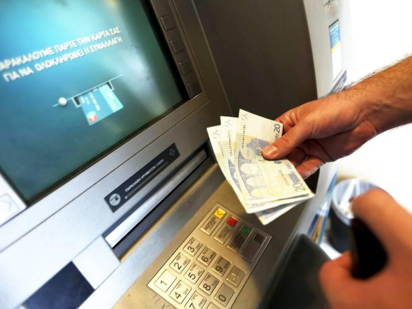 Homem saca 60 euros, o limite máximo diário para saque em um caixa eletrônico em Piraeus, próximo a Atenas, na Grécia. Nesta terça-feira (30) termina o prazo para que o país pague uma parcela de 1,6 bilhão de euros ao FMI - 30/06/2015