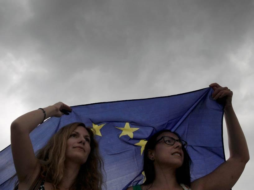 Manifestantes se protegem da chuva com uma bandeira da União Europeia durante protesto em apoio à permanência do país na zona do euro, em frente ao parlamento em Atenas, Grécia - 30/06/2015