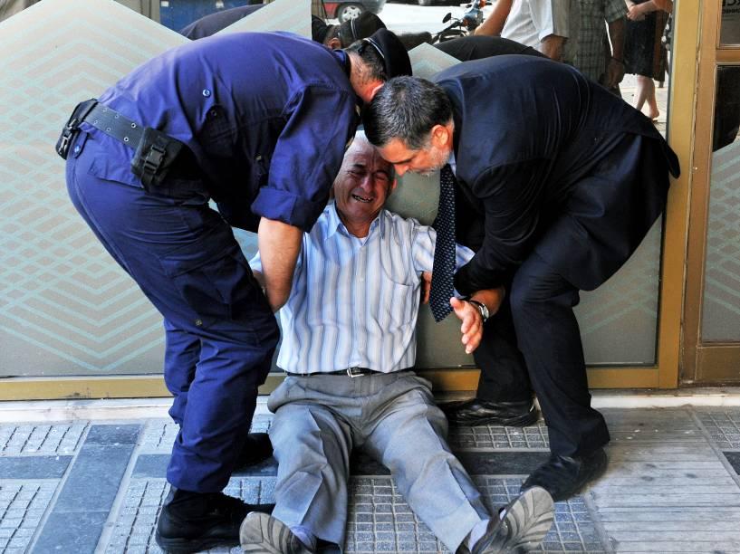 Aposentado grego chora na fila em agência bancária em Atenas nesta sexta-feira (3) após governo permitir que eles façam saques acima de limite imposto