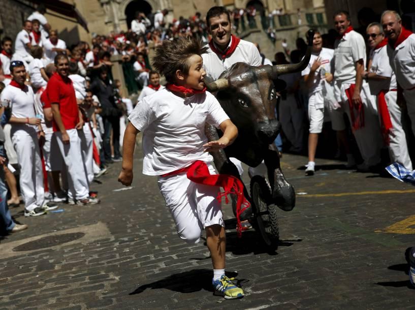"""Garoto é perseguido por um touro de brinquedo durante o """"Encierro Txixi"""", a """"pequena corrida dos touros"""", no Festival de São Firmino, em Pamplona - 09/07/2015"""