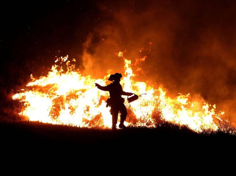 """Bombeiro tenta controlar as chamas do incêndio que ficou conhecido como """"Rocky Fire"""", em Clearlake, Califórnia. Cerca de 3.000 bombeiros enfrentam o incêndio que já queimou cerca de 60.000 acres e forçou a evacuação de 12.000 residentes"""