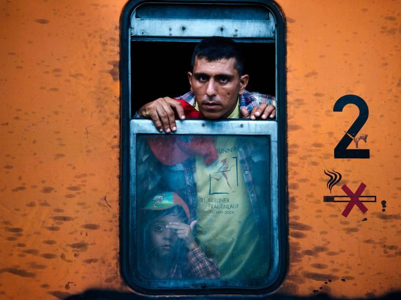 Imigrante olha da janela de um trem, com seu filho ao lado, enquanto segue em direção à Sérvia na cidade de Gevgelija, Macedônia - 03/08/2015