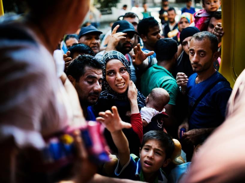 Imigrantes esperam para receber alimentos distribuídos por voluntários na estação de trem em Gevgelija, na fronteira da Macedônia com a Grécia. Muitos imigrantes tentam cruzar a Macedônia e a Sérvia para entrar na União Europeia pela Hungria - 04/08/2015