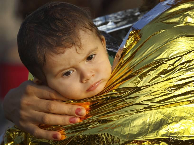 Criança refugiada síria é carregada no colo enrolada em um cobertor térmico no porto de Kos, após uma missão de resgate na ilha grega. Guarda Costeira italiana resgatou 60 refugiados sírios à deriva em um bote entre a Grécia e a Túrquia