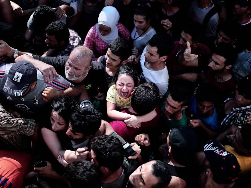 Criança chora em meio a uma multidão de imigrantes, durante um procedimento de registro em um estádio, na ilha grega de Kos - 11/08/2015