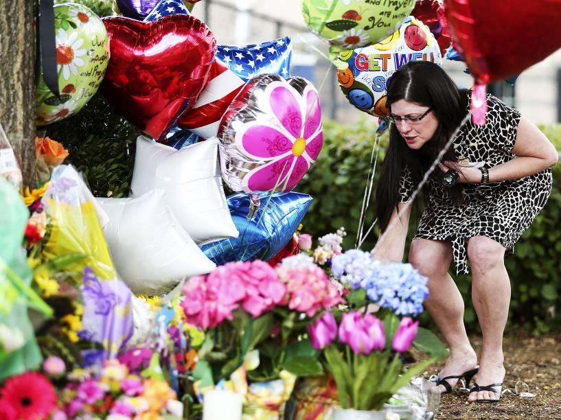 Mulher deixa flores em um memorial em frente à sede da WDBJ7 em Roanoke, Virgínia, nos EUA. Uma repórter e um cinegrafista da emissora foram mortos durante uma transmissão ao vivo após serem baleados por Vester Flanagan, um ex-funcionário da TV