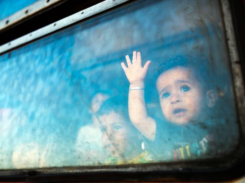 Menino imigrante olha da janela de um trem com destino à Sérvia na fronteira entre a Grécia e a Macedônia, perto da cidade de Gevgelija - 28/08/2015