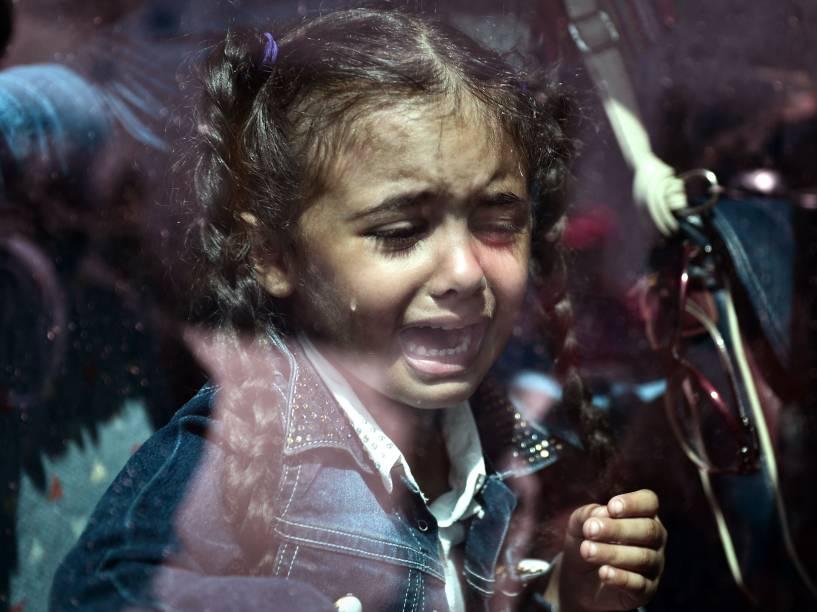 Criança refugiada chora dentro de um ônibus lotado transportando imigrantes e refugiados às estações de metrô e trem, após desembarcar de uma balsa do governo no porto de Pireus, em Atenas, Grécia - 08/09/2015