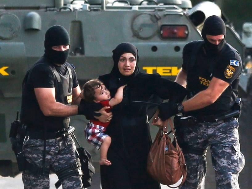 Policiais levam mulher e criança migrantes durante confronto em Roszke, na Hungria, nesta quarta-feira (16)