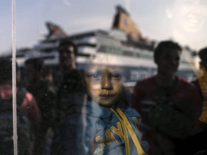 Menino imigrante é fotografado em um ponto de descanso depois de chegar ao longo da madrugada à ilha grega de Lesbos, vindos da Turquia em um bote inflável
