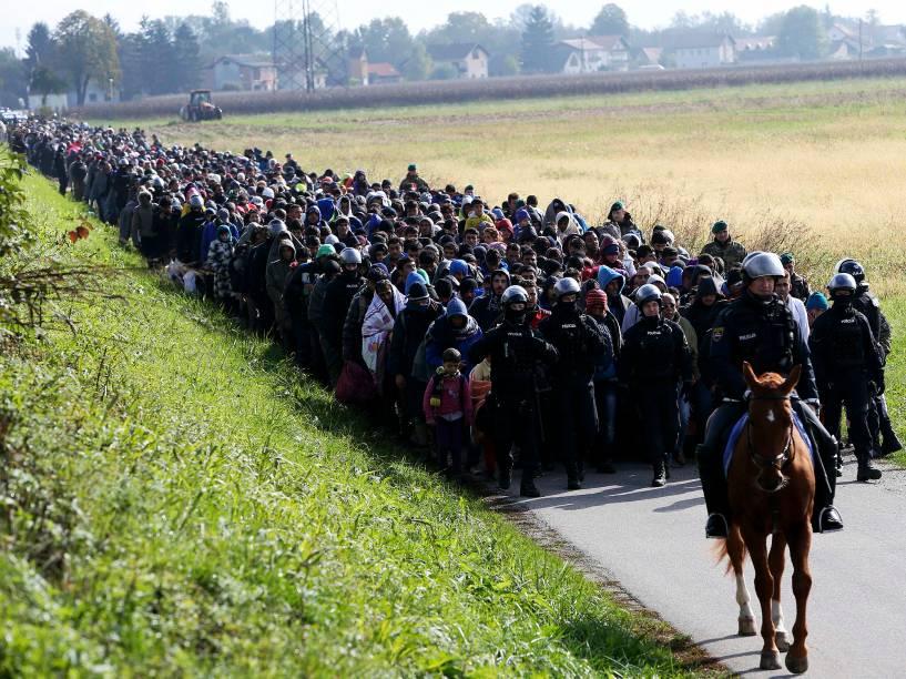 Policiais escoltam imigrantes próximo à fronteira entre a Croácia e a Eslovênia, nesta terça-feira (20)